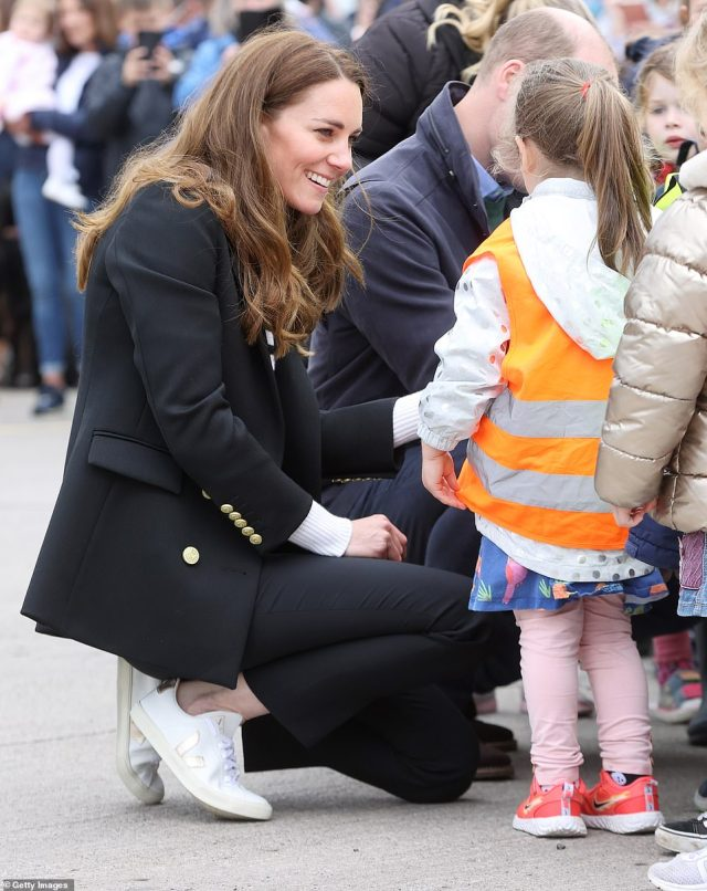 On their level: The Duchess of Cambridge crouched down to speak to the children on the outing in Fife today