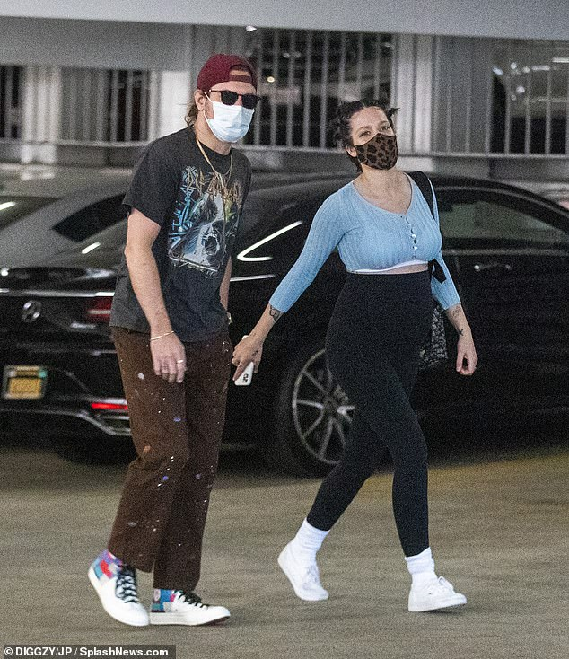 Taking care of business: The 26-year-old singer showed off a growing baby bump in a crop top and slacks while running errands in Los Angeles