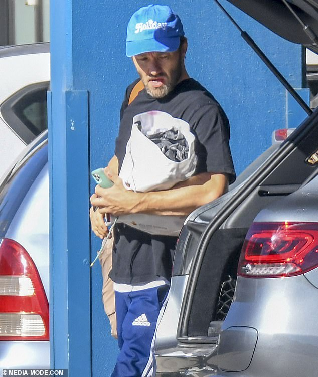 Style:He also teamed his ensemble with a blue cap and held a beige bag on his shoulder as he walked towards the gym