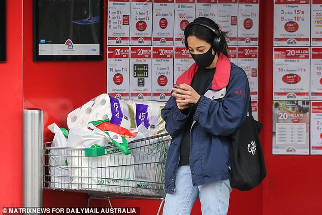 There were 11 new infections on Thursday bringing the total number of active cases of community transmission to 26 (pictured, a Melbourne shopper stocks up before the lockdown)