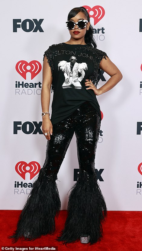 Sequins: She styled the graphic tee with a pair of sequin-covered flared trousers with ostrich feathers