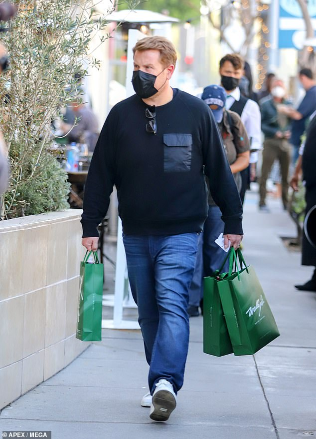 Out and about:The TV presenter, 42, kept his look casual in a navy jumper and blue jeans as he left the store laden with green shopping bags