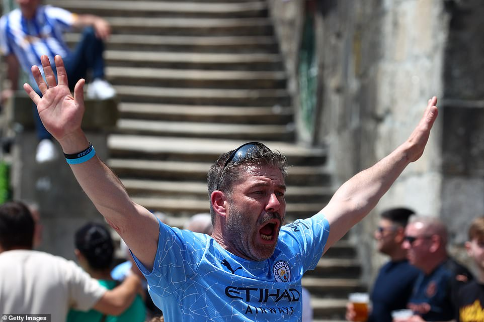 One Manchester City fan raises his arms as he chants in anticipation for the big match on Saturday night