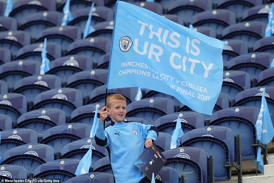 A young Manchester City fan waves a sky blue flag reading 'This is our City' as he entered the Estadio do Dragao stadium in Porto