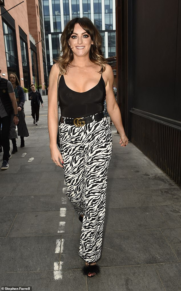 Fashion statement:Katie coupled her top with a striking pair of zebra-print bottoms tied off with a black and gold Gucci belt