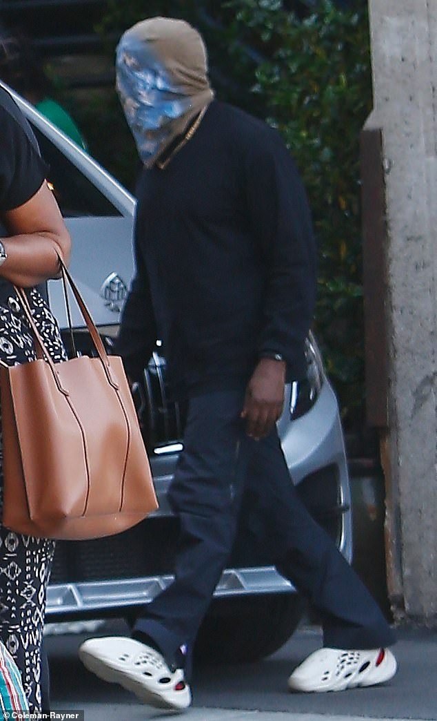 Ringless: Kanye West, 42, was glimpsed without his wedding ring as he attempted to go incognito under a bizarre looking face mask on a solo outing in Los Angeles