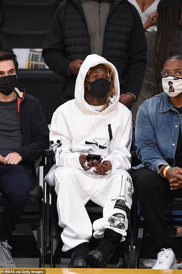 Game on! Lil Wayne appeared riveted by the match as he sat front row with a face mask covering his complexion