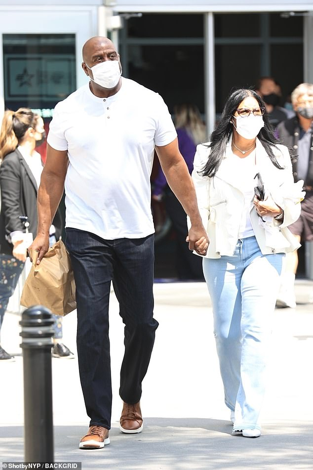 Doing the heavy lifting: Johnson carried a brown bag as he walked hand-in-hand with his stylish other half