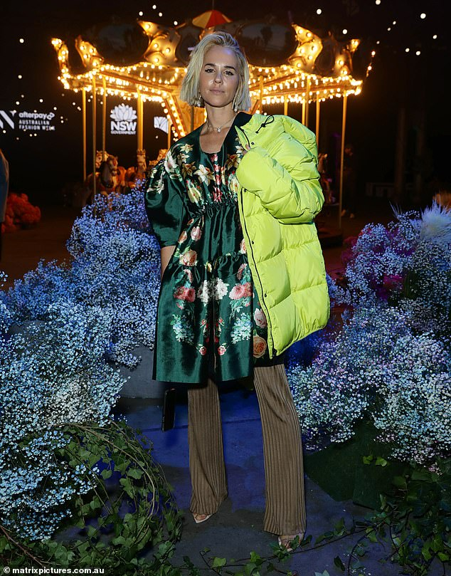 Fashion-forward: The P.E Nation co-founder covered up her figure in an emerald green floral shift dress, paired with slinky brown straight-leg pants and open-toe heels