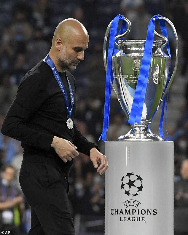 Guardiola makes a painful walk past the Champions League trophy after losing to Chelsea