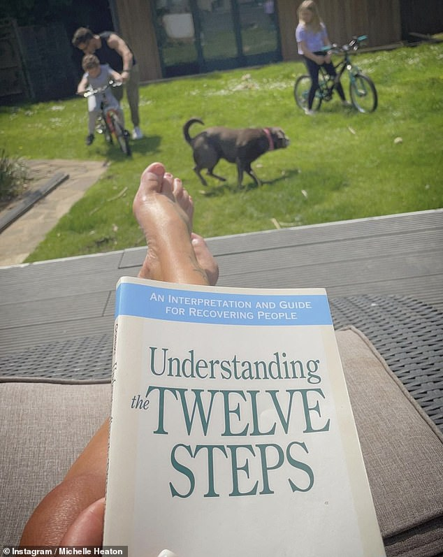 At home: The doting mum also took to Instagram on Sunday to share a snap of herself reading Understanding The Twelve Steps in the garden while watching her children play on their bikes