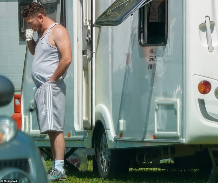 A man stands outside a caravan yesterday as the travellers continue to stay on the green, which is a short walk from Kew Gardens