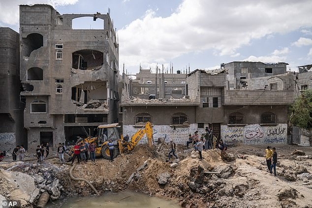 Neighbors gather to watch the cleanup of a crater full of water and sewage after the home of Ramez al-Masri was destroyed by an air-strike prior to a cease-fire reached after an 11-day war between Gaza's Hamas rulers and Israel, Sunday, May 23, 2021, in Beit Hanoun, the northern Gaza Strip