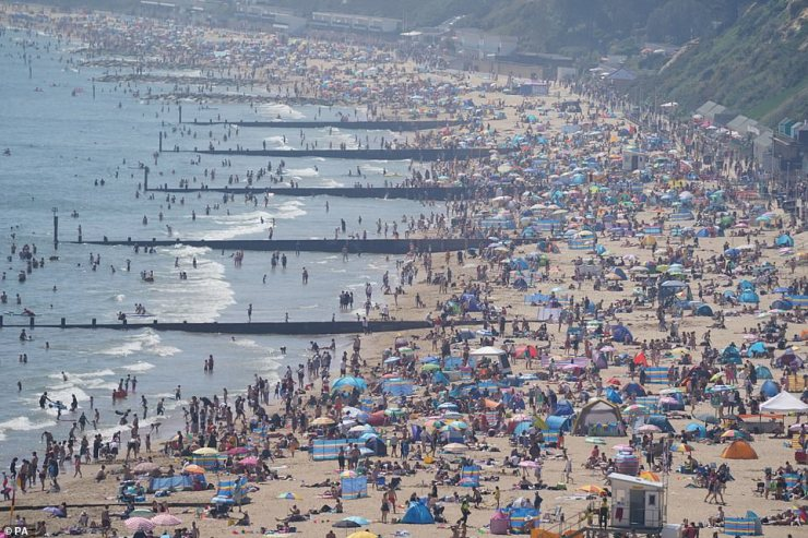 People enjoy the hot weather on Bournemouth beach this afternoon as they flock to the Dorset coast on bank holiday Monday