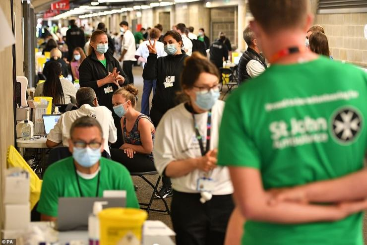 People queue up to receive a coronavirus vaccination at Twickenham rugby stadium in South West London yesterday