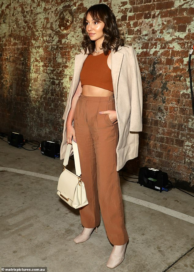 Fashionable: The 26-year-old did not seem affect by the autumn chill as she flaunted her toned stomach in a brown midriff top with a high waisted trousers and an oversized blazer