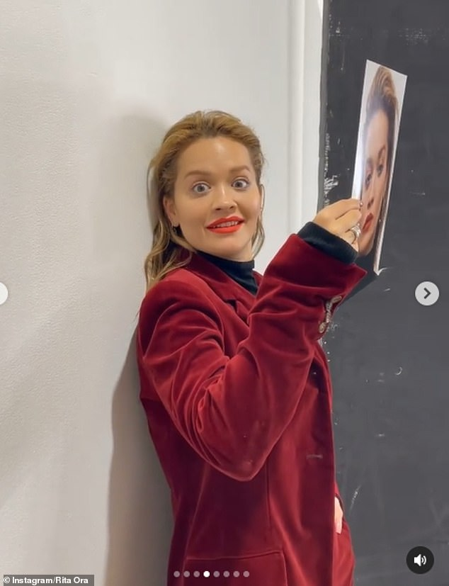 Two-faced: Finally, she was seen in a velvet blazer in red, with matching lipstick, larking around behind a headshot of herself