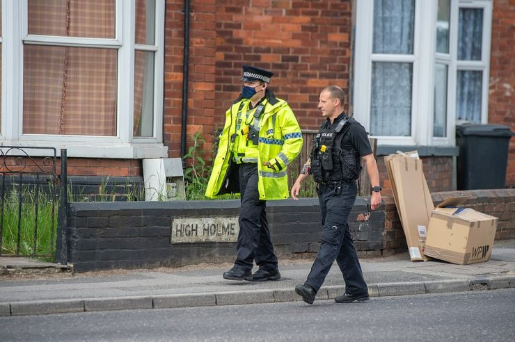 Police were seen walking along the road where a woman and child were found death yesterday