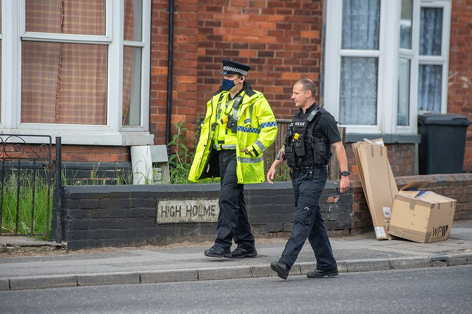 Police were seen walking along the road where a woman and child were found dead yesterday