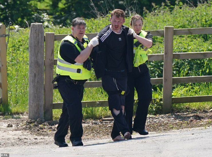 Pictures showed Boulton being arrested by two police officers who escorted him from a woodland area (pictured)