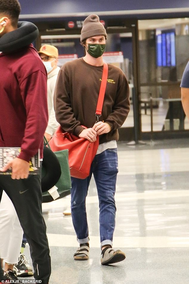 Chill:Chase donned a brown sweater with blue skinny jeans, black socks, brown double-strapped Birkenstock sandals, and a beanie