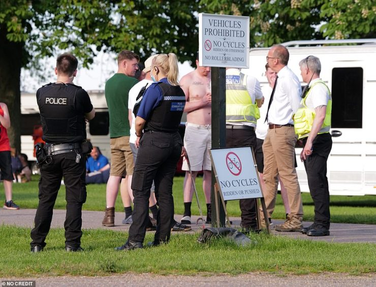 Last night, officials launched an attempt to move the travellers on, with pictures showing police, council officials and Windsor Park wardens (pictured) all in discussions with the group