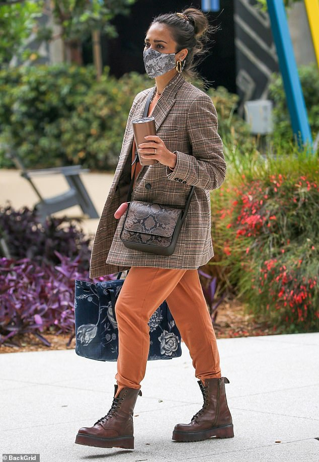 Power suit: She paired the cozy-looking burnt orange lounge set with stylishly distressed platform Doc Martens and rocked a patterned face mask and gold hoop earrings