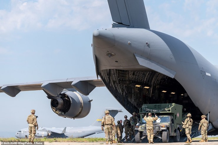 U.S. Air Force Airmen assigned to the 435th Contingency Response Group support personnel and heavy equipment offload from a C-17 Globemaster III aircraft during exercise Swift Response 21 at Cheshnegirovo Airfield in Bulgaria