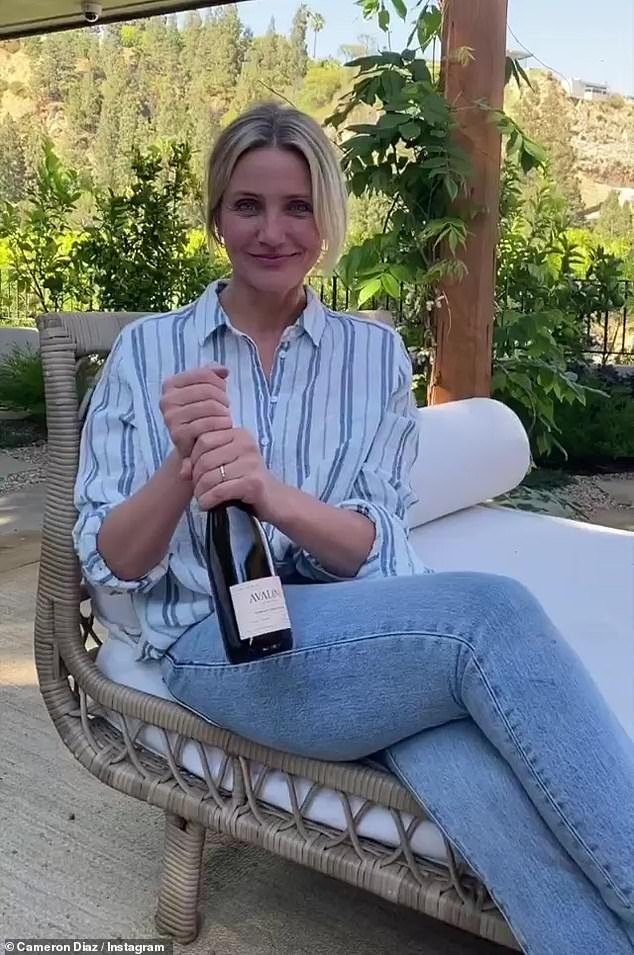Glowing: The video begins with Diaz, dressed in faded blue jeans and a white and blue striped shirt, sitting outside by herself with a big beaming smile and a bottle of Avaline in hand