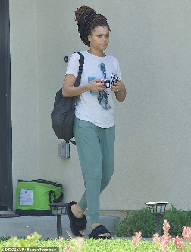 Casually clad: Andra (born Cassandra Monique Batie) dressed down in a white T-shirt emblazoned with a guitar illustration, green sweatpants, and black fuzzy slides