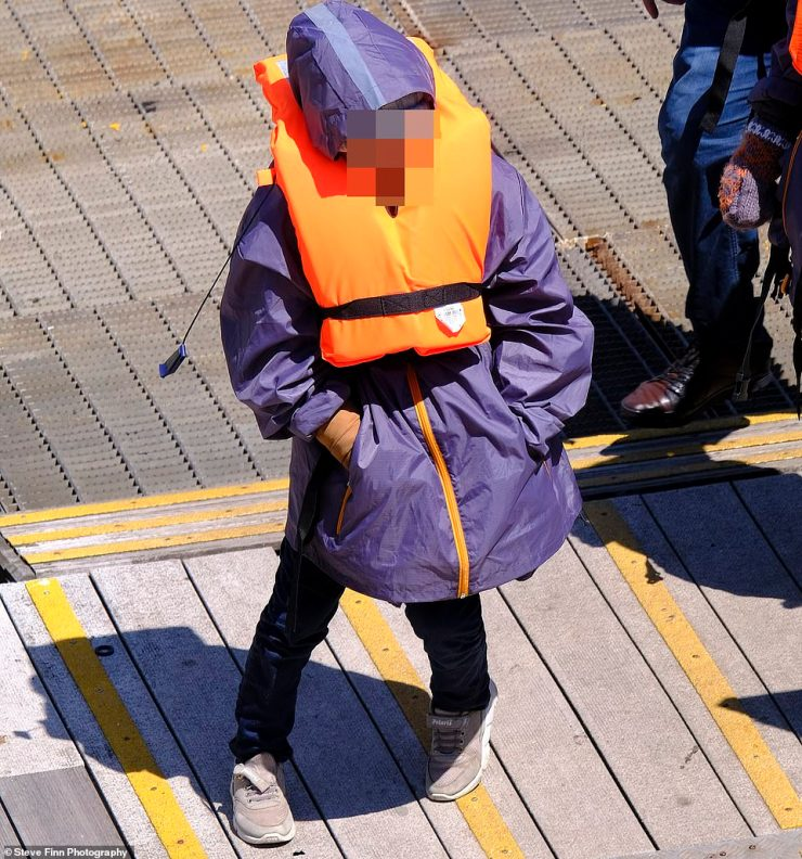 A child is pictured at Dover Marina yesterday after an estimated 200 migrants arrived at the Kent coast