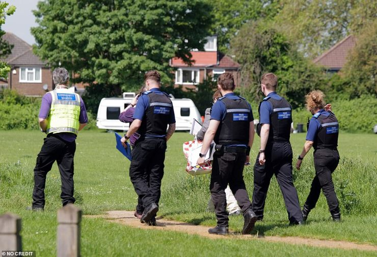 Officials with clipboards are seen walking along a path in Dedworth, where a group of travellers moved to after relocating out of Windsor's Long Walk