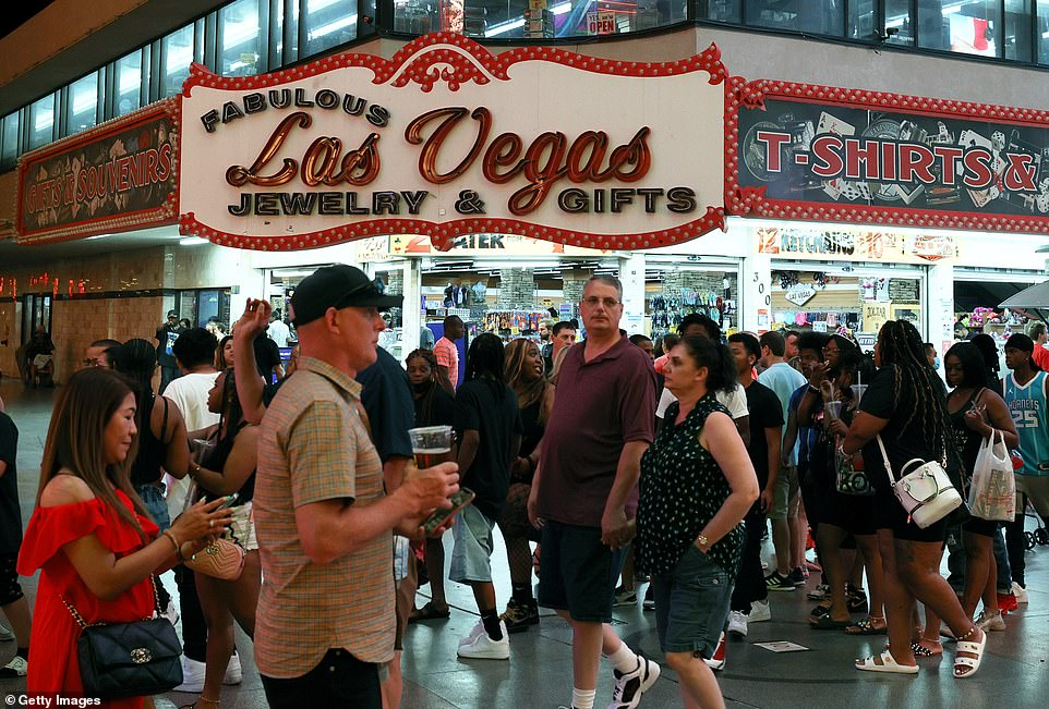 Visitors walk by a gift store at the Fremont Street Experience on June 1. People who are vaccinated don't have to wear masks in the city any longer, with few exceptions