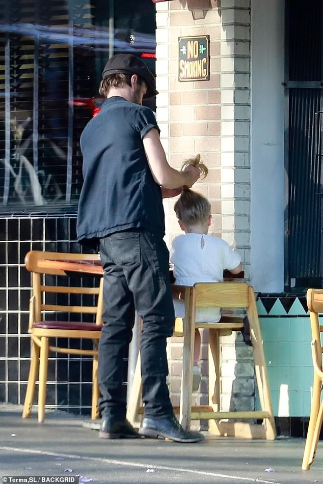 Helping hand:The cutest moment came when the 41-year-old actor stood up to twist his only child's hair into a messy bun before enjoying their meal