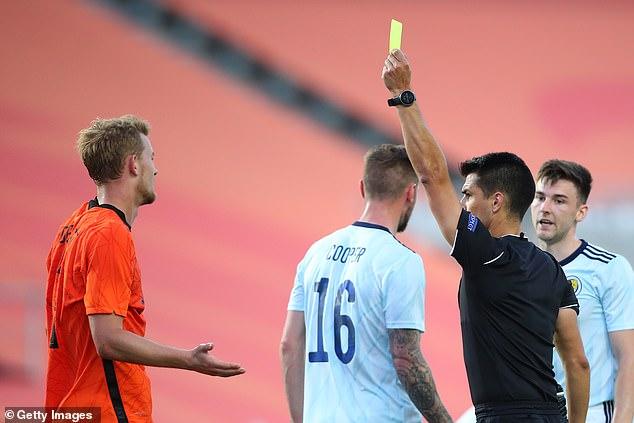 Vitor Jorge Fernandes Ferreira brandishes a yellow card towards Juventus' Matthijs de Ligt
