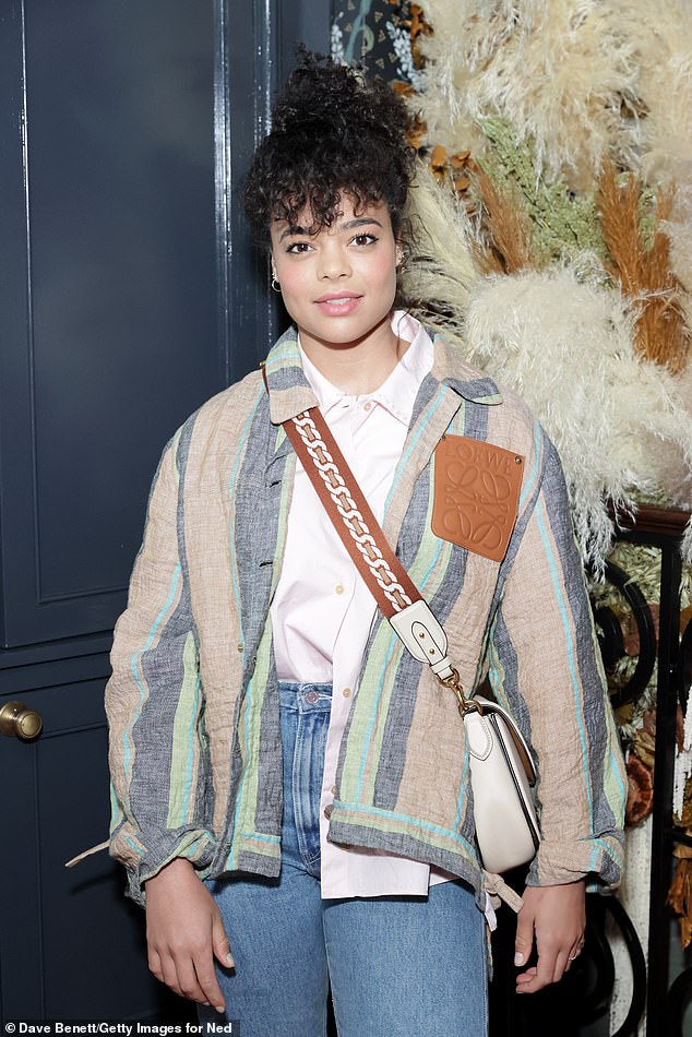 Style: The star paired her outfit with blue mom jeans and a salmon and grey striped Loewe patterned jacket