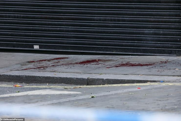 SHEPHERD'S BUSH: And in Shepherd's Bush in west London, blood-soaked pavement is seen as police stand by a cordon following a stabbing