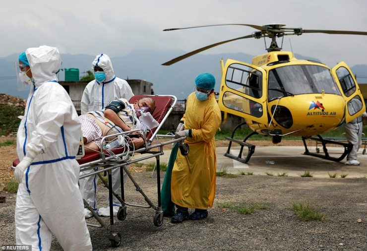 Health workers carry Ramjee Kunwar, 65, a Covid-19 patient from a helicopter to an ambulance after being airlifted from Pokhara to Kathmandu due to health complications