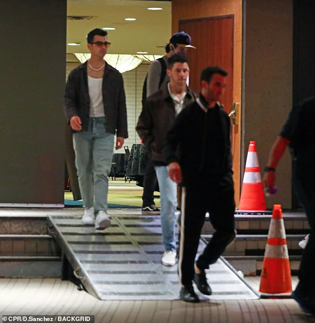 Style:Nick cut a casual figure in a black bomber jacket which he paired with blue jeans and a white shirt