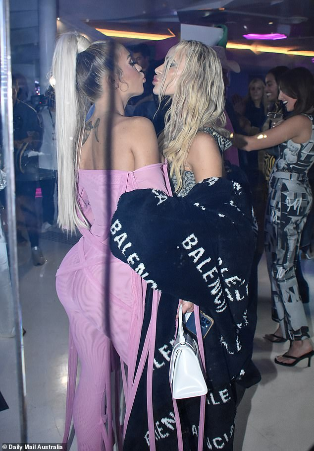 Pals:Tammy appeared quite festive as she laid a smooch on the blonde woman, who had on a black Balenciaga coat