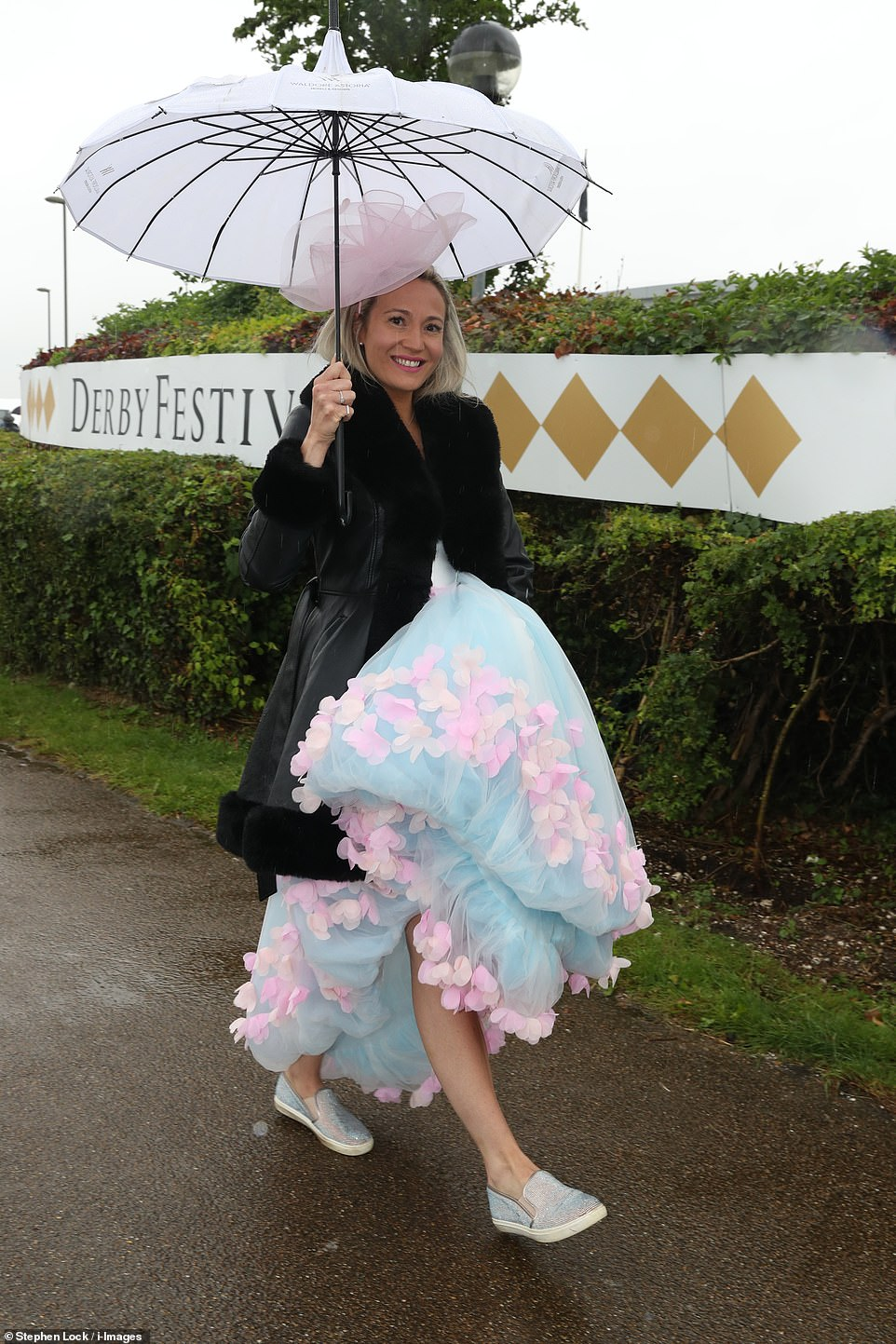 Not put off: It might have been raining but that didn't stop many racegoers from ramping up the glamour in her sparkly shoes and pastel-coloured dress