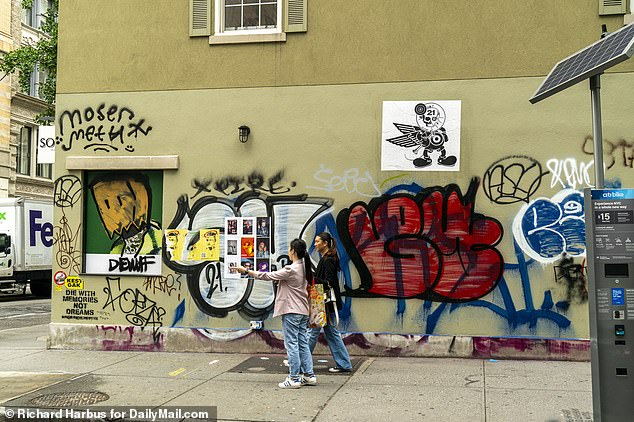 New Yorkers walk past defaced walls in what was once the hottest shopping destination in the city for residents and tourists