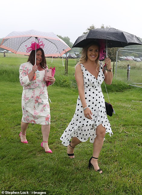 Connect the dots! Two racegoers were all smiles as they traipsed through the wet grass
