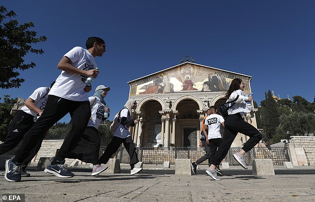 Palestinian activists pass the Gethsemane church as they take part in a local marathon in solidarity with Sheikh Jarrah families and against the eviction of the Palestinian families from their homes in Sheikh Jarrah neighborhood in favor of Jewish families