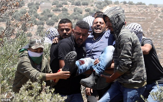Palestinian protesters evacuate a wounded man during clashes with Israeli troops after a protest against a new Israeli settelment built over Palestinian lands near Beita village, near the West Bank City of Nablus, 04 June 2021