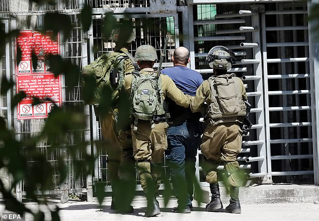 Israeli army soldiers arrest a Palestinian following scuffles during clashes with Palestinian stone throwers in the West Bank city of Hebron, 04 June 2021.