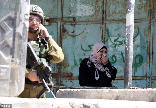 Pictured: A woman covers her face with her head scarf as she watches IDF troops during clashes withPalestinians at the city center of the West Bank city of Hebron, 04 June 2021
