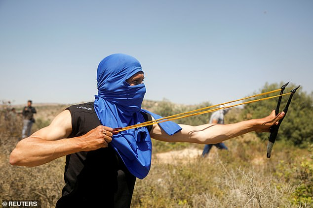 A Palestinian demonstrator uses a slingshot to hurl stones at Israeli forces during a protest against Israeli settlements in Beita, in the Israeli-occupied West Bank June 4, 2021