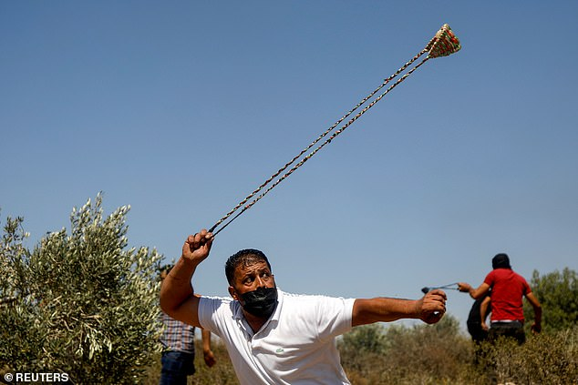 Pictured:A Palestinian demonstrator uses a sling to hurl stones at Israeli forces during a protest against Israeli settlements in Beita, in the Israeli-occupied West Bank June 4, 2021