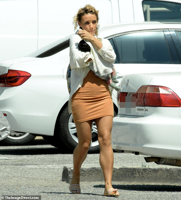 Switching out: Although she was initially seen wearing a pair of distressed blue jeans, the model later donned a light orange miniskirt and a white cardigan sweater